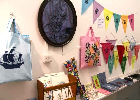 Pop up shop interior with vinyl stickers, prints and bunting flags